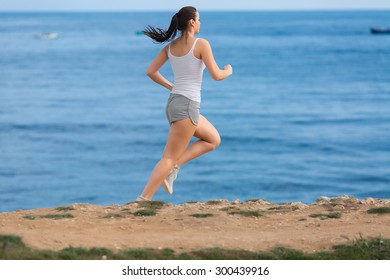 Jogging. Woman in jeans shorts and  white tank top runs along seashore