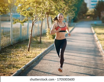 Jogging woman running in park in sunshine on beautiful summer day. Sport fitness model of mixed caucasian ethnicity training outdoor for marathon.
