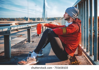 Jogging. Young sportsman siting on the ground and take a little break after training outdoor. Fitness, sport, lifestyle concept