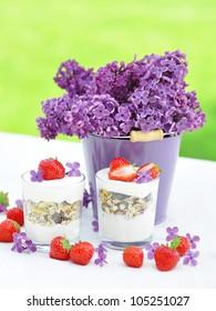 Joghurt und M�¼sli in Becher mit Erdbeeren auf einen Gartentisch. Dekoriert mit Fliederstrau��.