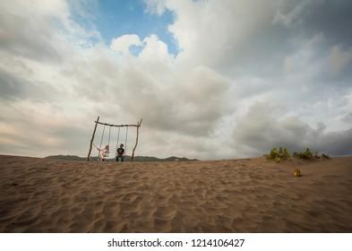 Jogjakarta, Indonesia  09/2017  : People enjoying swing in Gumuk Pasir, a popular tourist destination in Jogjakarta.