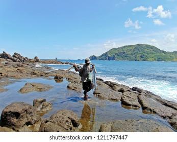 Jogjakarta, Indonesia. April, 2017: A fisherman is carrying his catch in Wediombo Beach, Gunung Kidul