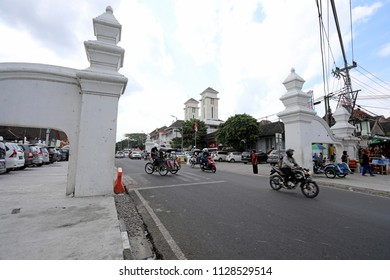 Jogjakarta, Indonesia - June 22, 2018: Motorbikes and rickshaws pass through a gateway leading into the Sultan's Palace complex in Jogjakarta