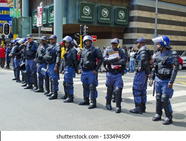 JOHANNESBURG - FEBRUARY 3: Police officers stand guard over protesting crowds in Johannesburg on February 3, 2013. S A policemen killed 34 striking miners at  Marikana mine on August 16, 2012.