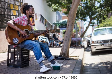 Johannesburg, Gauteng, South Africa, 20018/01/10. A Busker singing and playing guitar on the streets of Johannesburg.  An African man playing the guitar in the streets.