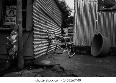Johannesburg, Gauteng / South Africa - April 22 2019: old steel chair in a shack environment midday ramaphosa township