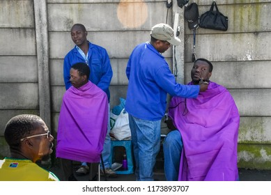 Johannesburg , Gauteng / South Africa -august 31 2012 : two men getting their hair cut and trimmed on a sidewalk  midday Rosettenville Johannesburg