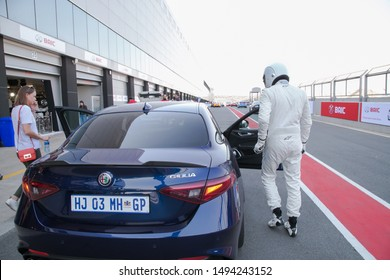 Johannesburg, Gauteng, South Africa August 25 2019 The stig top gear at race track getting in a alfa car in a white racing suit with helmet outside