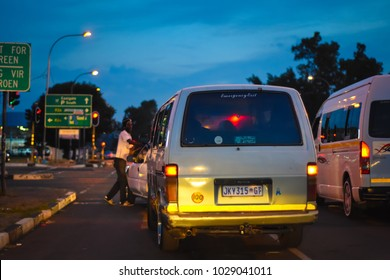 Johannesburg, Gauteng / South Africa - Dec 20 2017: Taxi stopped at red light, at night. traffic,dark sky,passengers travelling in the combi,rear view