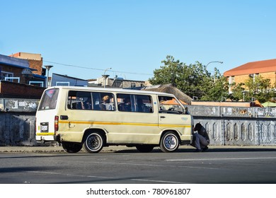 Johannesburg, Gauteng / South Africa - Dec 22 2017: taxi driver check the front of Taxi while customers wait to be transported to their destination,common low cost transportation used in johannesburg