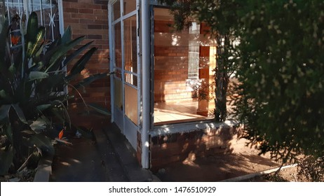 Johannesburg, Gauteng / South Africa - july 15 2019 :  trees obscuring an empty sunroom space early morning light Foresthill Johannesburg