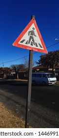 Johannesburg, Gauteng / South Africa - june 20 2019 :  walkway warning sign against blue sky and a white african taxi driving past in the background