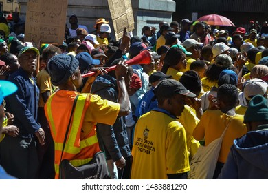 Johannesburg, Gauteng / South Africa - May 02 2019 :  african man blowing a vuvuzela in a crowd at a political march midday johannesburg