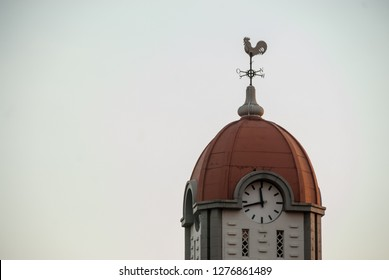 Johannesburg , Gauteng / South Africa - november 04 2018 : church tower with a clock and rooster weathervane sunset late afternoon alberton johannesburg