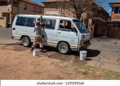 Johannesburg, Gauteng / South Africa - October 03 2018 :man washing a taxi in the street midday Johannesburg city