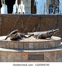"Johannesburg Gold Reef City. South Africa -December21,2013: Fountain & sculpture of two crocodiles with a memorial plaque with a sign ""This Fountain is dedicated to the twin brothers Solly & Abe Krok"