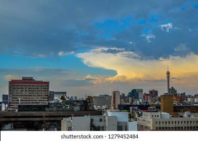 Johannesburg skyline under heavy clouds at sunset