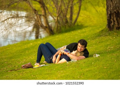 Johannesburg, South Africa, 05/10/2014, A couple relaxing on the grass at The Winter Sculpture Fair at Nirox Sculpture Park