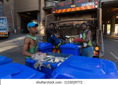 Johannesburg, South Africa, 15th June 2018. A street photo of a  group of african men busy putting garbage into a garbage truck with one of the men looking at the photographer, not visible.