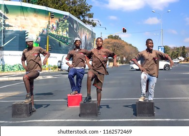 Johannesburg, South Africa, 19 August - 2018: Boys performing at traffic intersection with beer bottle crates.