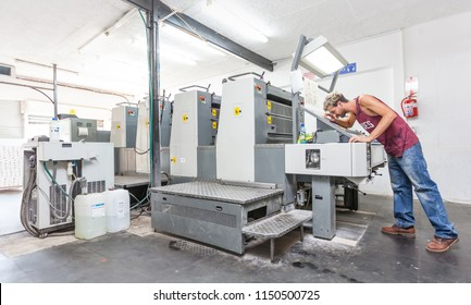 Johannesburg, South Africa, 26 March - 2017: Lithographic printing machine in a printing workshop. Operator looking at print.