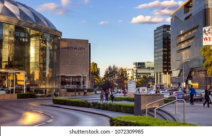 Johannesburg, South Africa, April 6 - 2018: Shopping mall entrance with busy road and pedestrians in evening light.