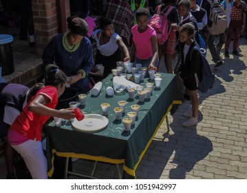 Johannesburg, South Africa - August 11, 2017: Unidentified underprivileged school children receive food handouts at a soup kitchen at their school in the city image in landscape format