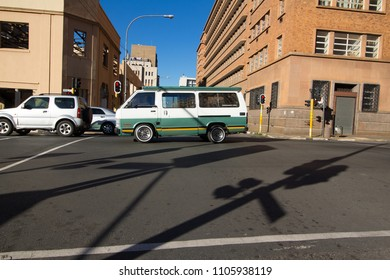 Johannesburg, South Africa, Circa June 2018, A mini bus taxi drives past a photographer, not visible  while the photographer takes the photograph of the taxi driving down the road.