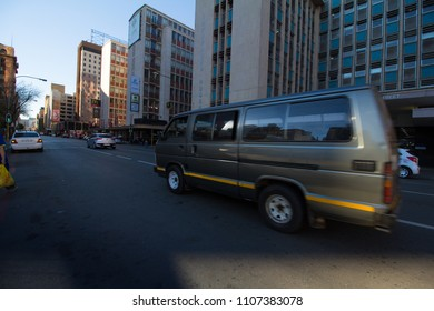 Johannesburg. South Africa, Circa, June 2018. A green taxi drives down the road in the Johannesburg city center with buildings in the background.
