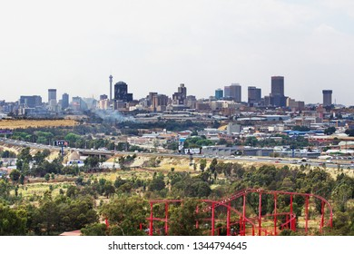 JOHANNESBURG, SOUTH AFRICA - CIRCA OCTOBER 2018: Aerial view of a roller coaster at an amusement park, with the the downtown skyline in the distance