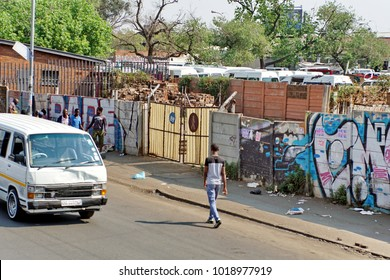 JOHANNESBURG, SOUTH AFRICA - CIRCA SEPTEMBER 2017: Workers on a sidewalk beside a township taxi stand