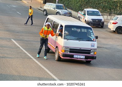 JOHANNESBURG, SOUTH AFRICA - CIRCA SEPTEMBER 2017: Man in a reflective vest beside a shared combi taxi in Newtown