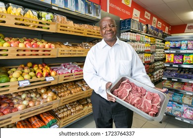 Johannesburg, South Africa - February 24, 2016: Owner manager posing with produce in isle at local Pick n Pay grocery store
