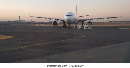 Johannesburg, South Africa - July 17 2019: A South African Airways aeroplane being pushed backward away from the airport gate by a pushback tractor on the runway at the O.R Tambo International airport