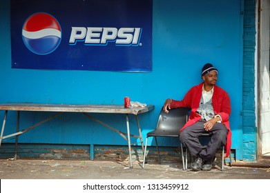 Johannesburg, South Africa July 2011 A customer enjoying a Coke at a convenient store, with the Pepsi brand painted on the wall in the background. Situated in Jules Street, Malvern, Johannesburg.