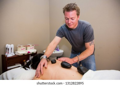 Johannesburg, South Africa - June 12 2013: Therapist using stones and massage in beauty salon