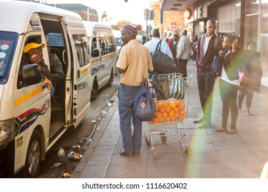Johannesburg, South Africa - June 7, 2018: Street vendor selling oranges at a taxi rank.