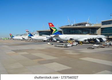 Johannesburg / South Africa - March 29 2019: South African Airways and Egyptair (African airlines) Airbus aircraft parked at O R Tambo International Airport passengers terminal. Air travel in Africa.