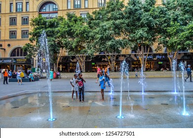 Johannesburg , South Africa - Nov 23 2018: Young African kids playing in fountain at Nelson Mandela square Piazza in Sandton