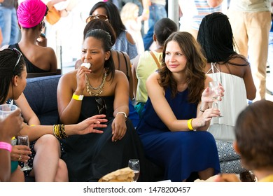 Johannesburg, South Africa - November 9 2013: Diverse Friends eating, drinking and generally enjoying a day out at a Food and Wine Fair