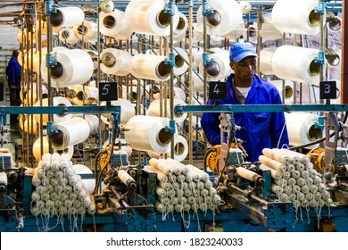 Johannesburg, South Africa - October 16, 2012: African factory worker on a copwinder weft assembly line loom