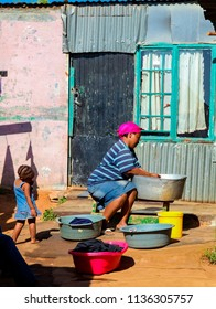 Johannesburg, South Africa, September 11, 2011, African mother and child washing clothes in Low-income Soweto neighborhood