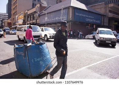 Johannesburg, South Africa,Circa June 2016, An African man walking in downtown Johannesburg while pulling a blue recycling cart.