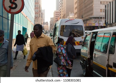Johannesburg, South Africa,Circa, June 2016. A photographer, not visible captures a candid street photo of commuters getting into a taxi.