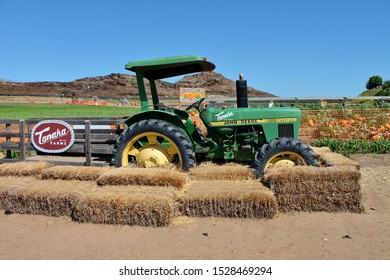 A John Deere farm tractor parked by haystacks at a Tanaka Farms pumpkin patch in California