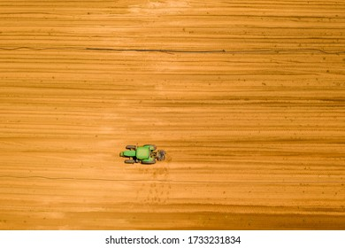 John Deere green Tractor in the middle of a large agriculture filed, Aerial image.