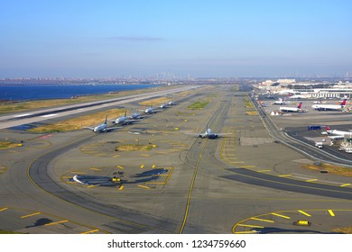 JOHN F. KENNEDY AIRPORT, NY -17 NOV 2018- Airplanes are lining up for take-off at John F. Kennedy International Airport (JFK), with the view of Manhattan, New York City in the background.
