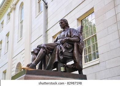 John Harvard statue in front of University Hall in Old Harvard Yard, Harvard University, Cambridge, Massachusetts MA, USA.