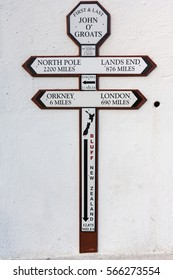 John O Groats, Scotland - June 5, 2012: Cross sign with the distances to different spots on the globe. The town considers itself the north point of the British Island. Black and brown on white wall.