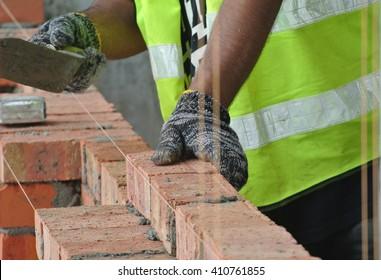JOHOR, MALAYSIA -APRIL 05, 2016: Bricklayer install clay bricks for building walls.